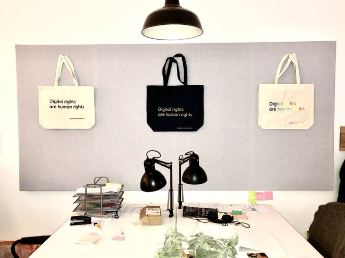 "photo of DFF office with collection of ""Digital rights are human rights"" tote bags hanging on wall"