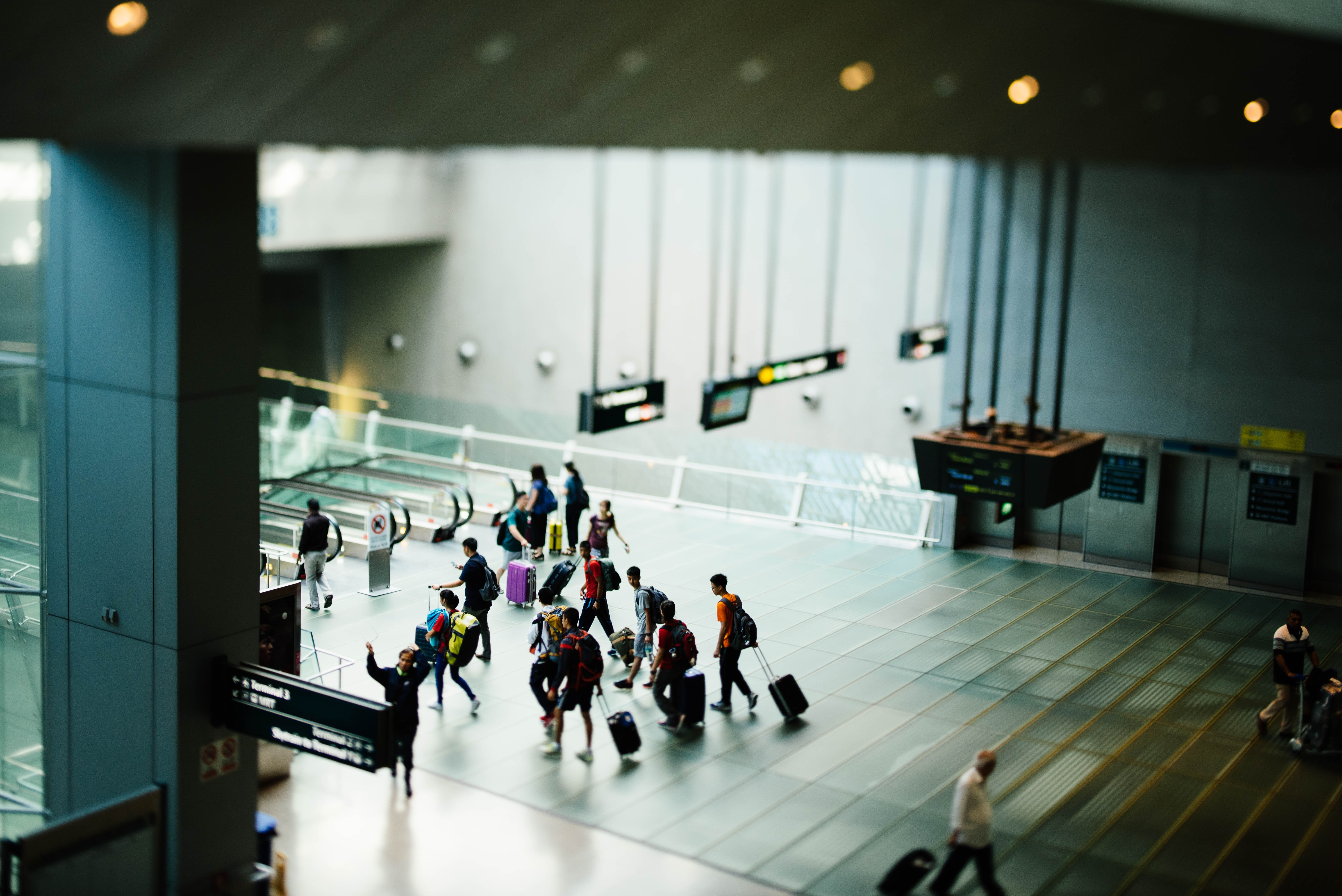 photo from above the inside of an airport terminal, passengers walking with suitcases
