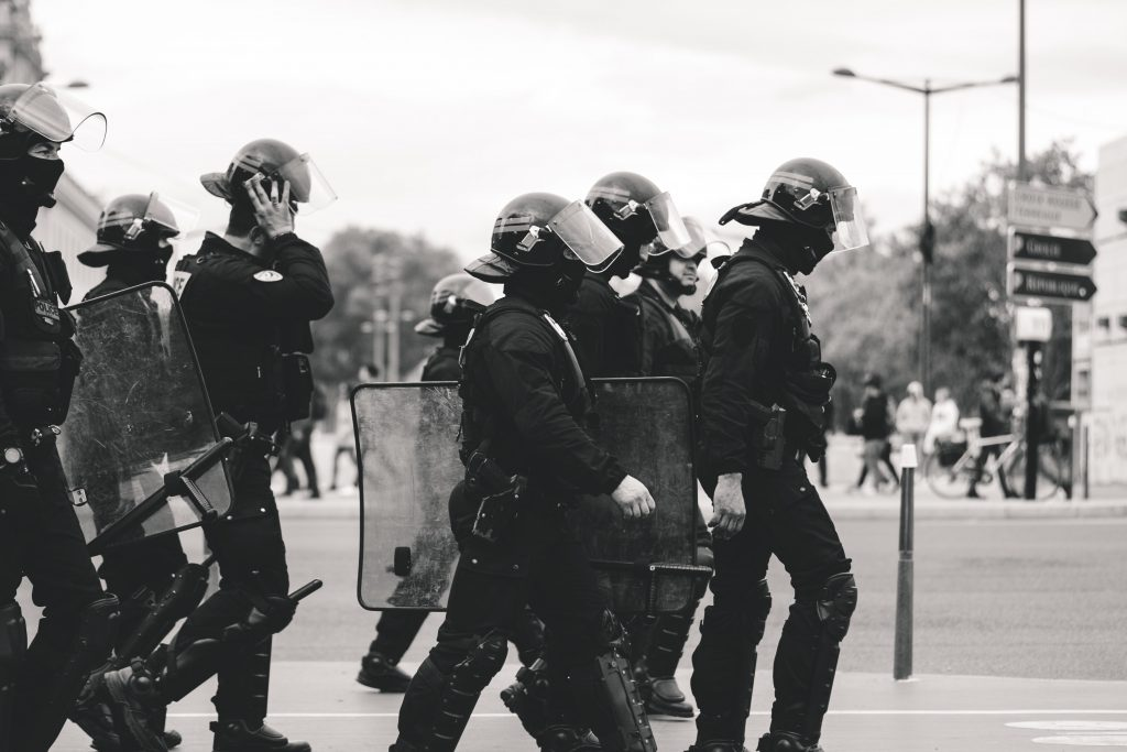 A group of police officers in riot gear make their way across a street.