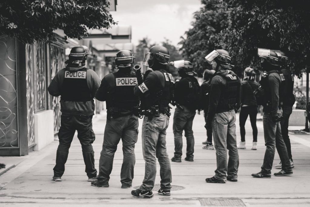 A group of police officers in riot gear standing on a street