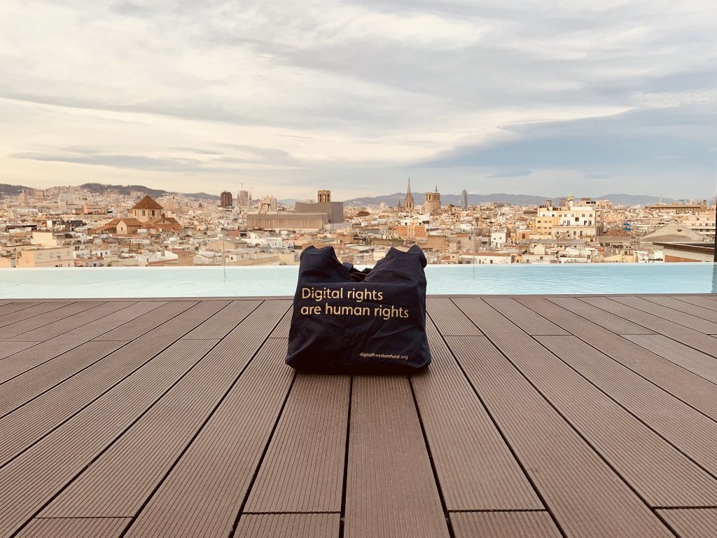A black DFF tote bag reads Digital Rights are Human Rights, sitting on a wooden floor looking over Barcelona