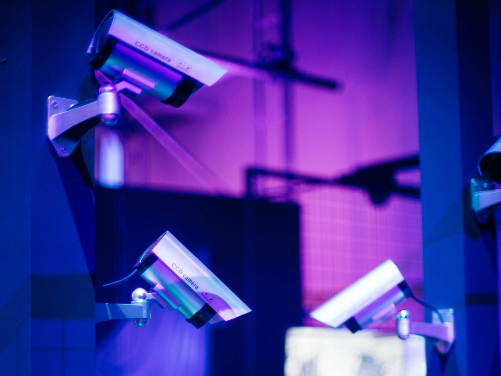 Stock image of surveillance cameras on a purple-blue background