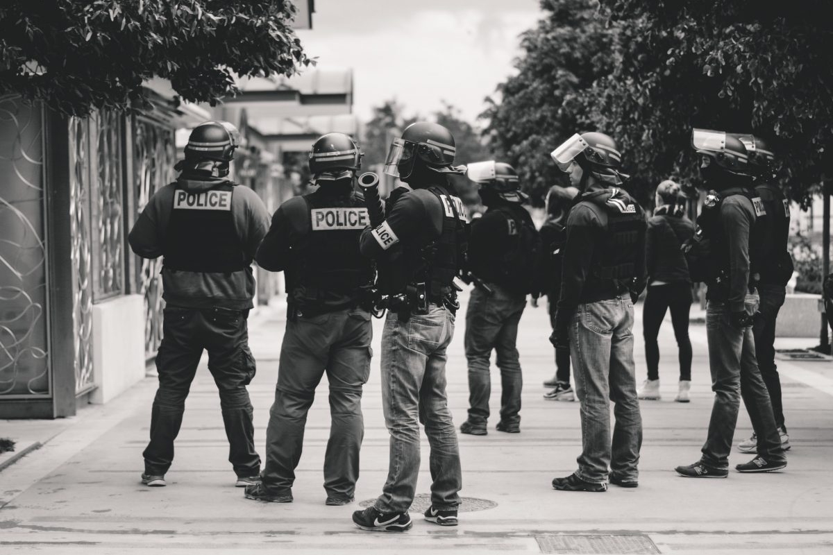 Black and white photo of several police standing around wearing helmets. Photo by ev on Unsplash