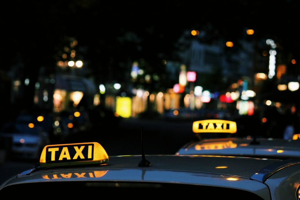 Two neon yellow taxi signs against the blurred lights of the city at night
