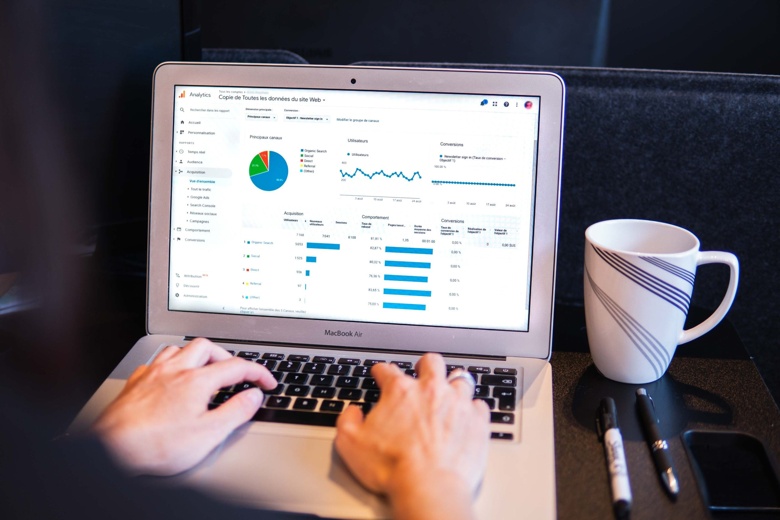 Somebody using a laptop with data and graphs on the screen. Photo by Myriam Jessier on Unsplash