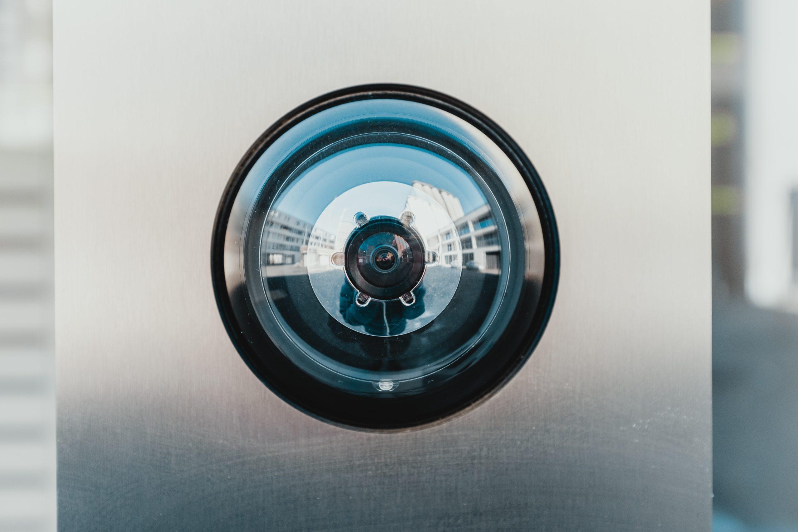 A close-up of a surveillance camera lens. Photo by Bernard Hermant on Unsplash