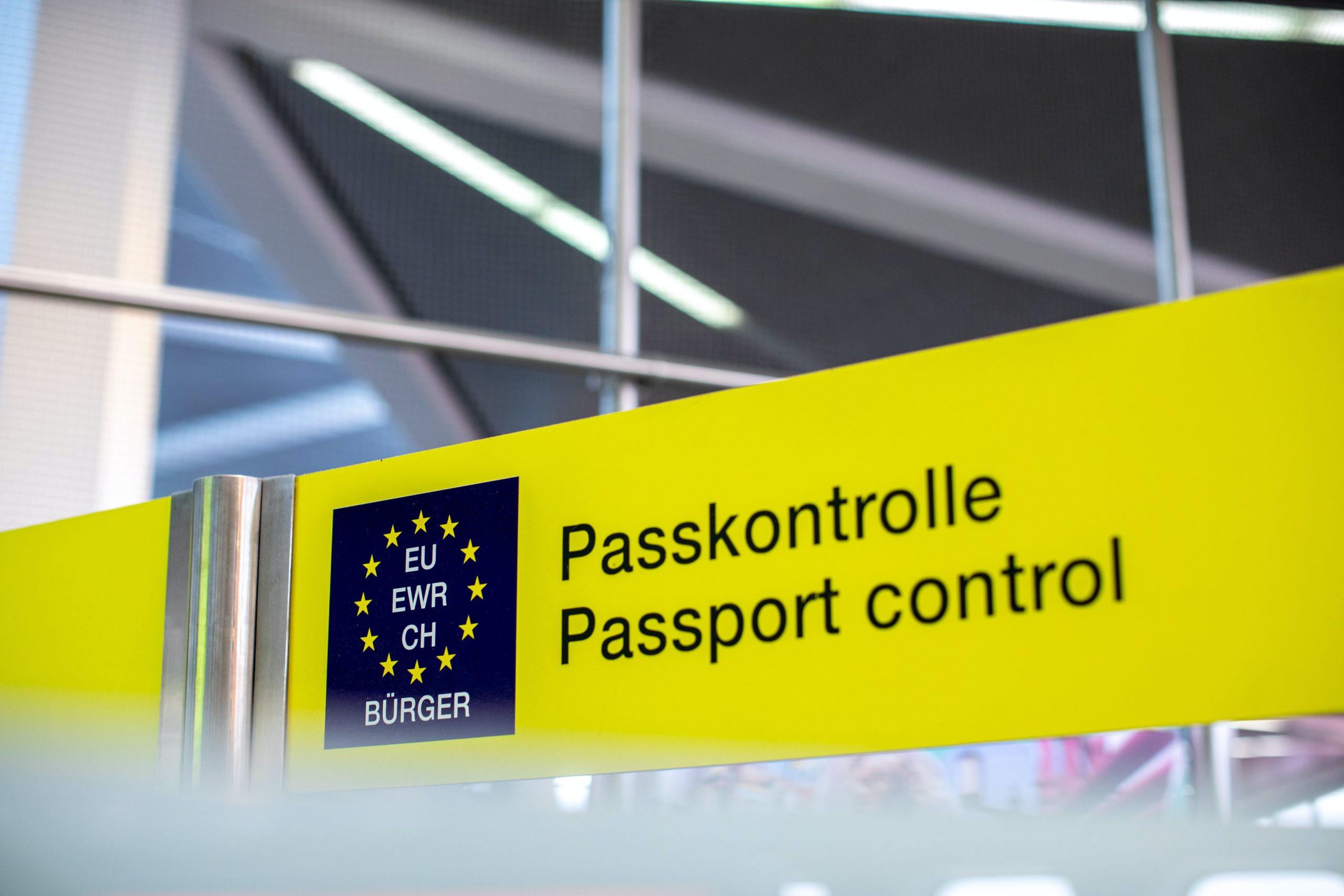 Airport sign reading Passport Control. Photo by Daniel Schludi on Unsplash