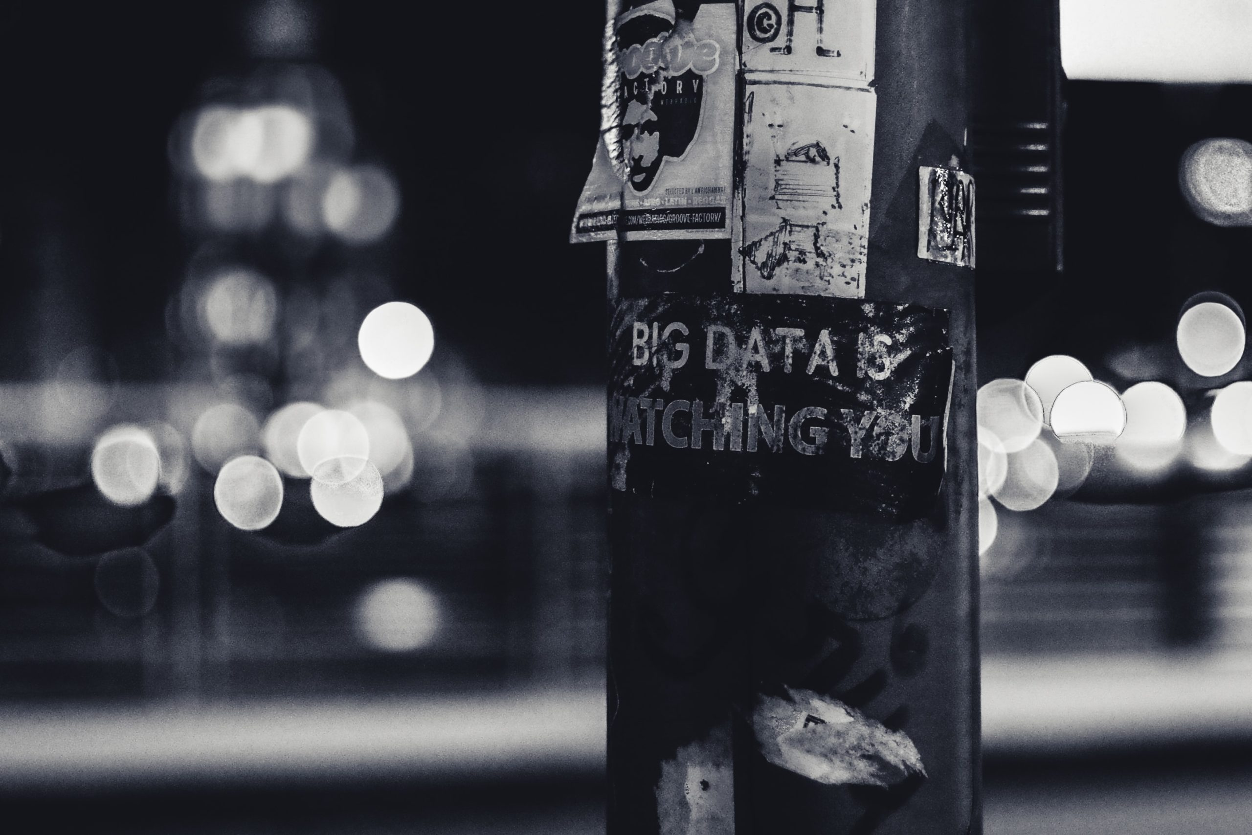 """Pole with sticker reading """"Big Data is Watching You"""". Photo by ev on Unsplash"""