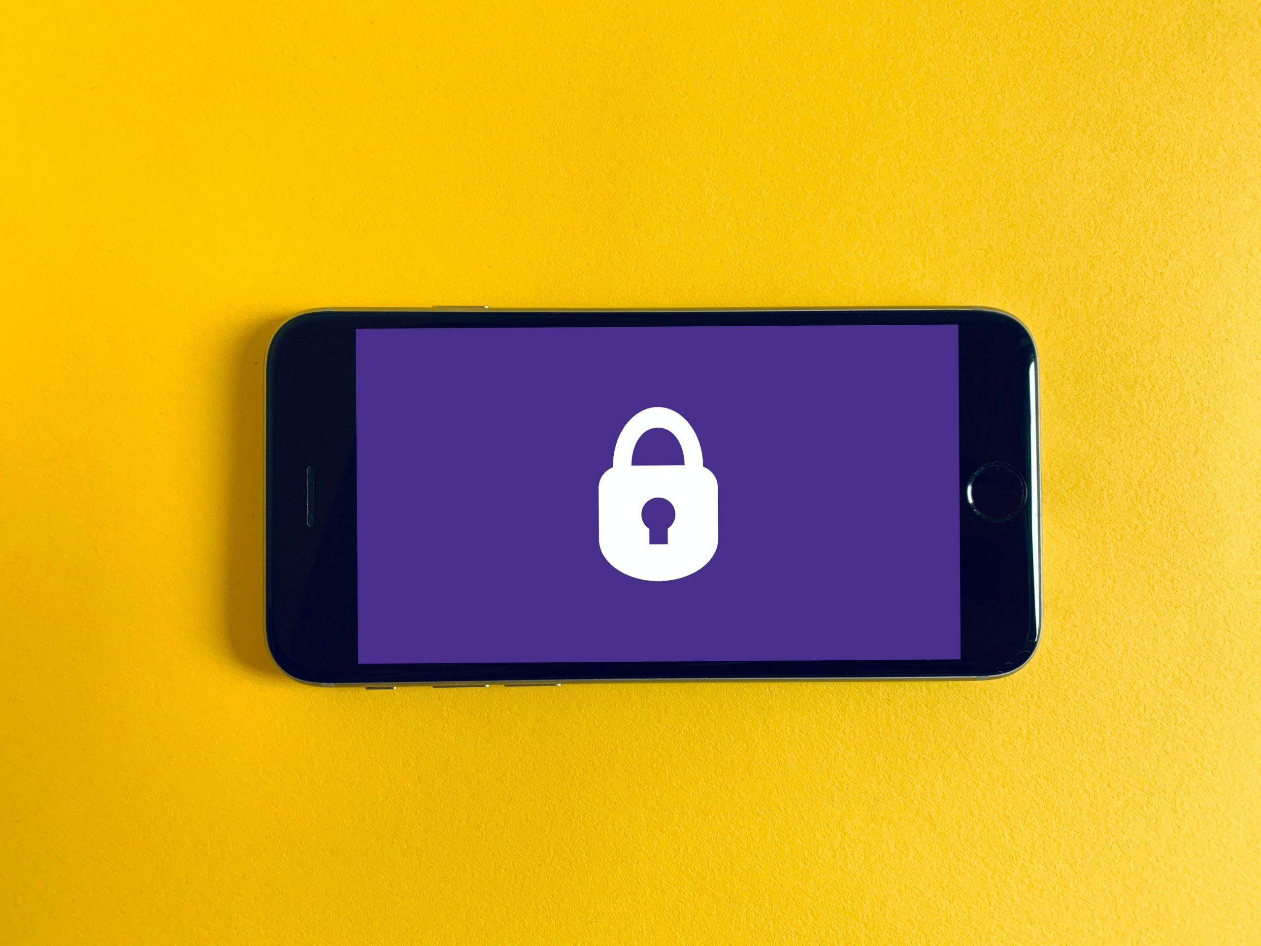 Smartphone with screen displaying white lock against purple background. Photo by Franck on Unsplash