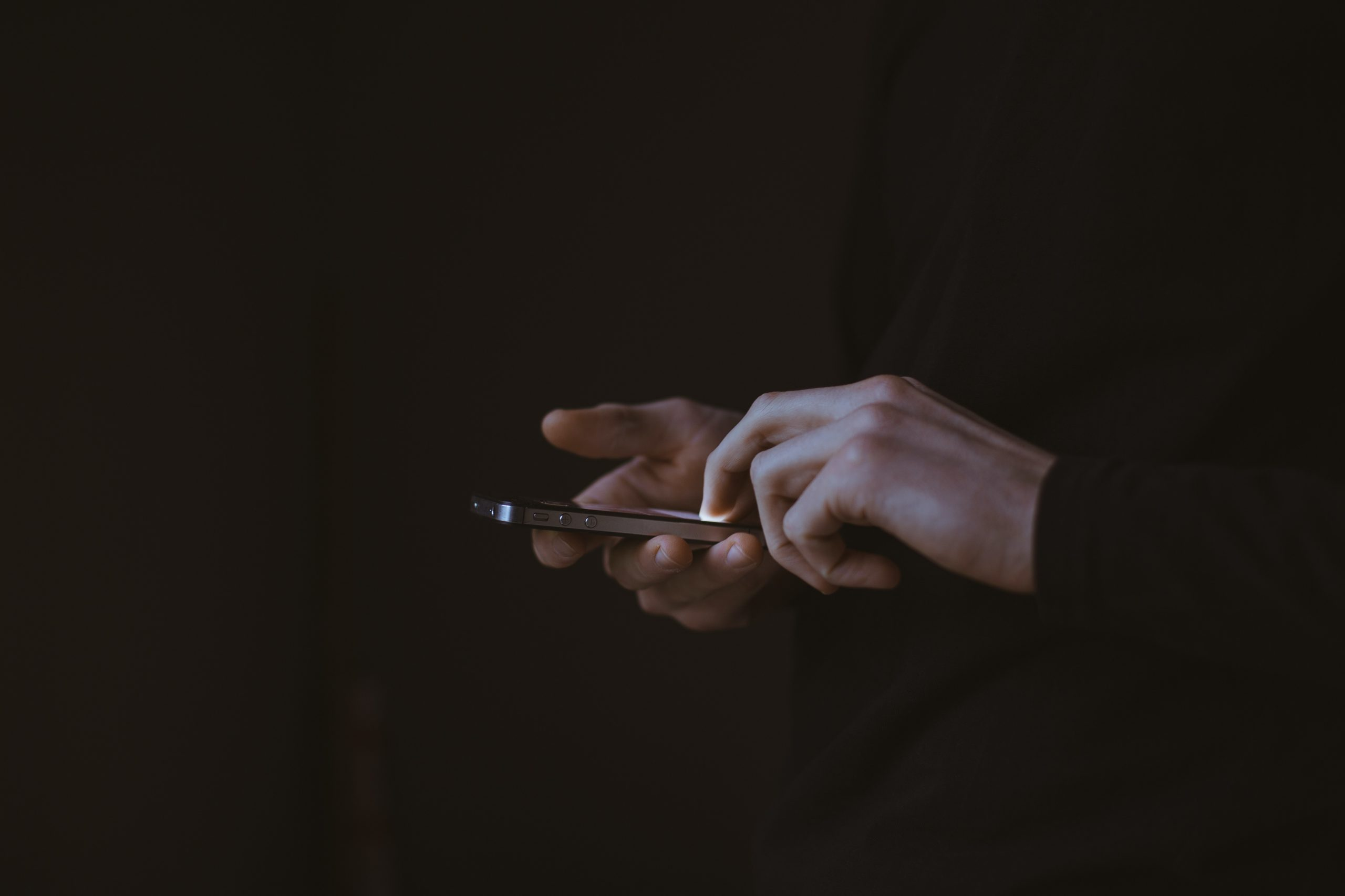 Two hands using a smartphone. Image by Gilles Lambert on Unsplash