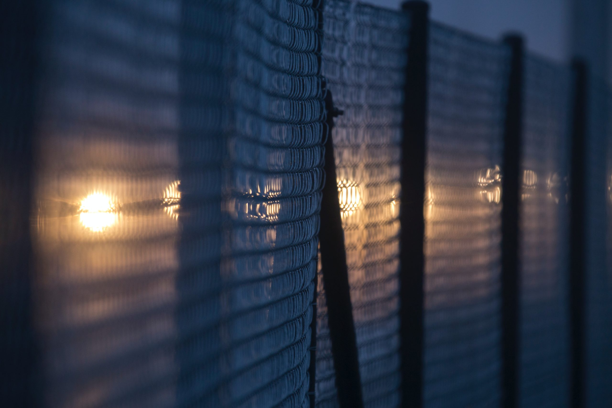 Wire fences at night with lights peaking through. Photo by Phil Botha on Unsplash