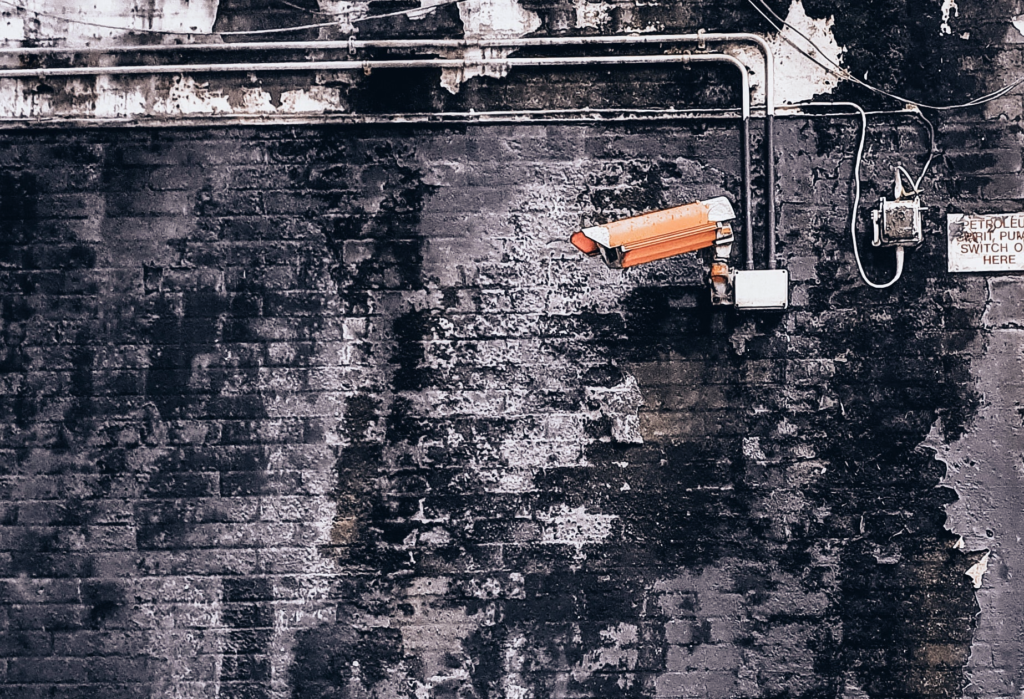 Orange security camera against a chipped brick wall