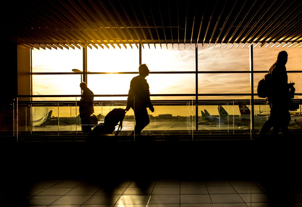 Silhouettes of people against airport windows