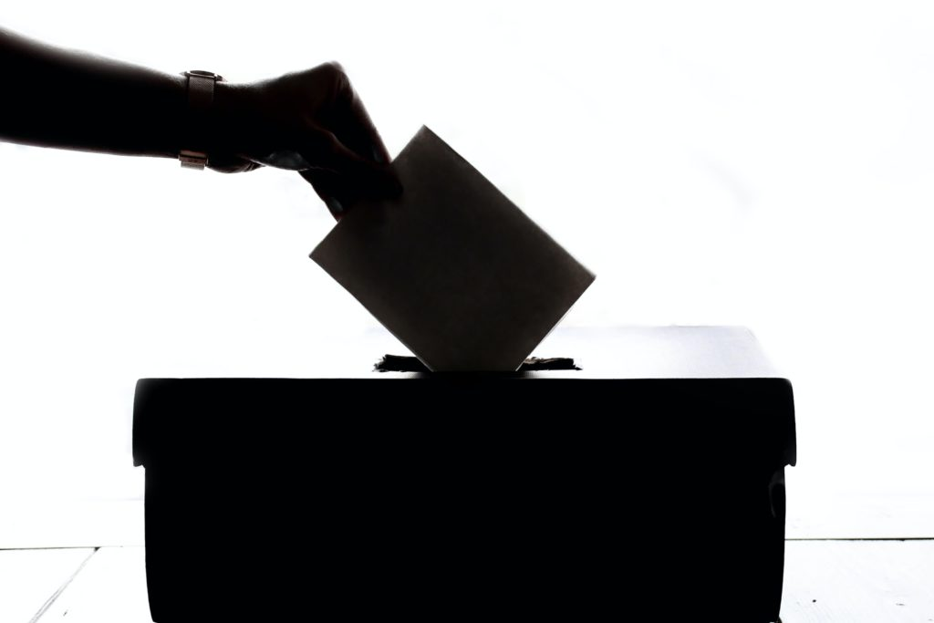 Stock photo of a hand putting a vote into a ballot box